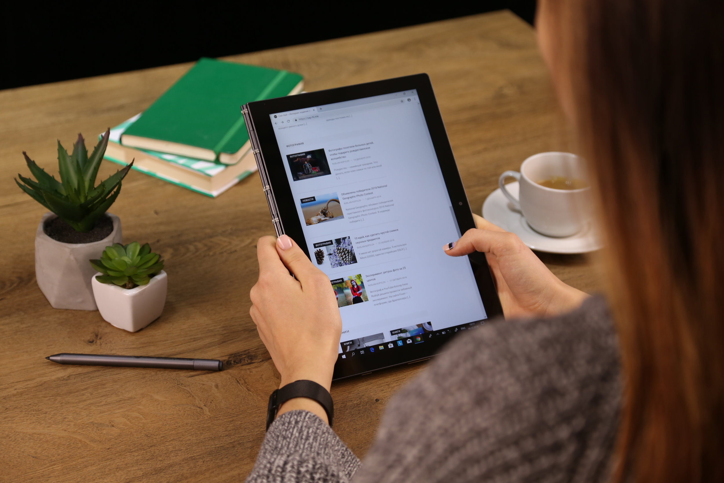 An over-the-shoulder shot of a woman scrolling through her iPad at a desk