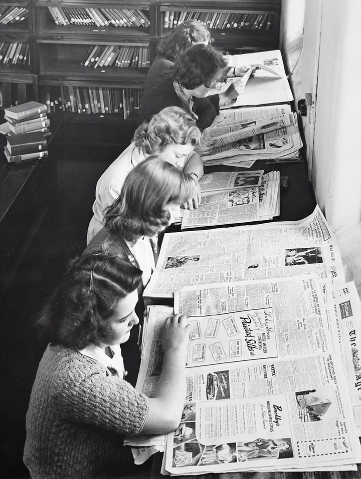 vintage photo of women reading newspaper in 1950s