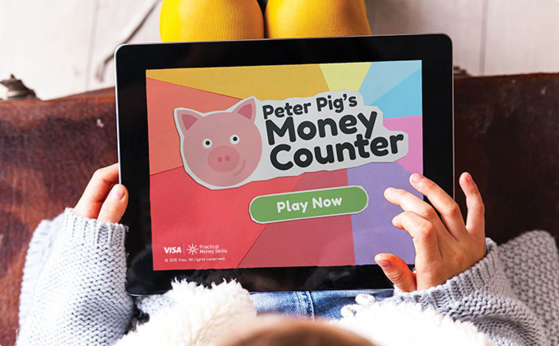 A small child plays the Peter Pig's Money Counter game on a tablet device.