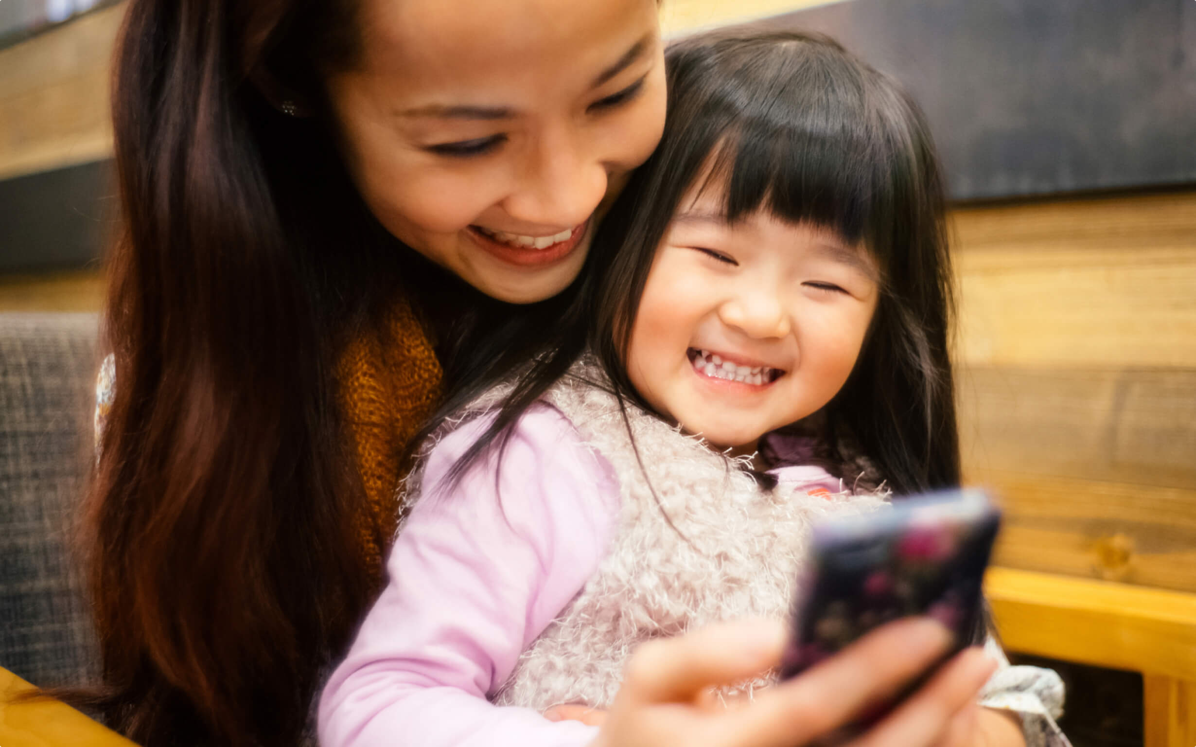 A woman and her small daughter smile while looking at a mobile phone.