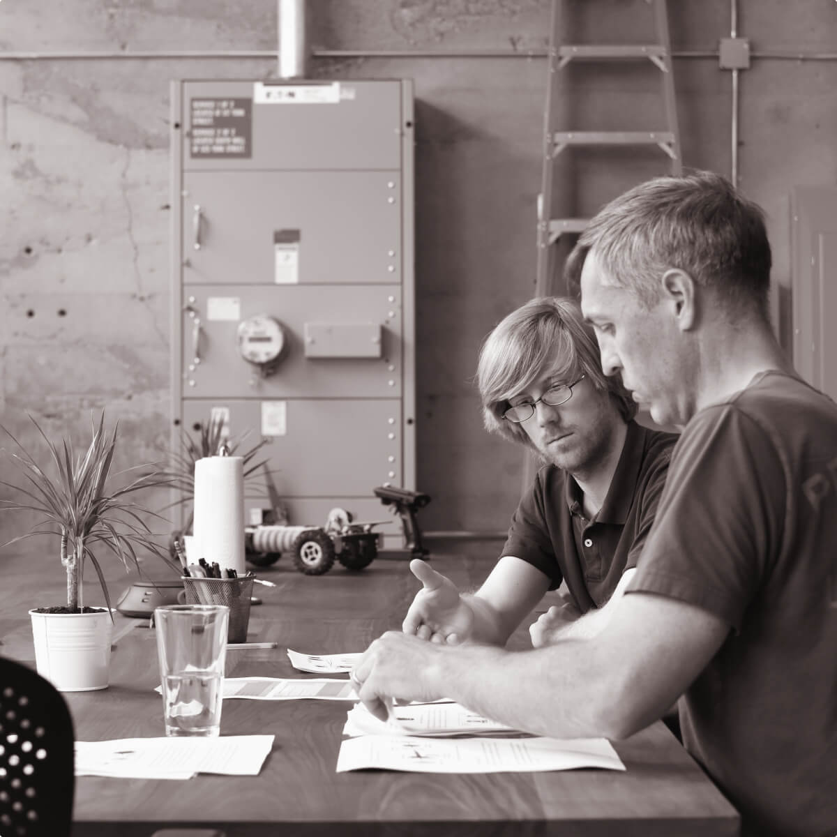 Two Cooper Perkins engineers sit at a desk and work together to solve a challenging problem.