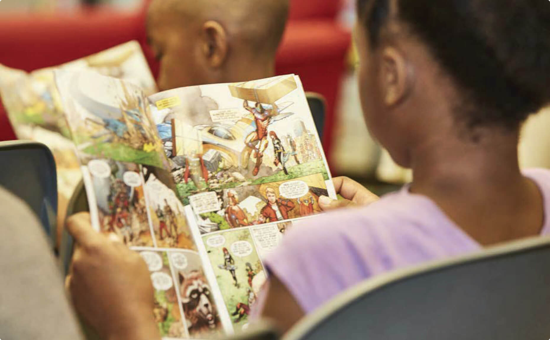An elementary school student reads an educational comic book featuring Marvel characters discussing financial literacy skills.