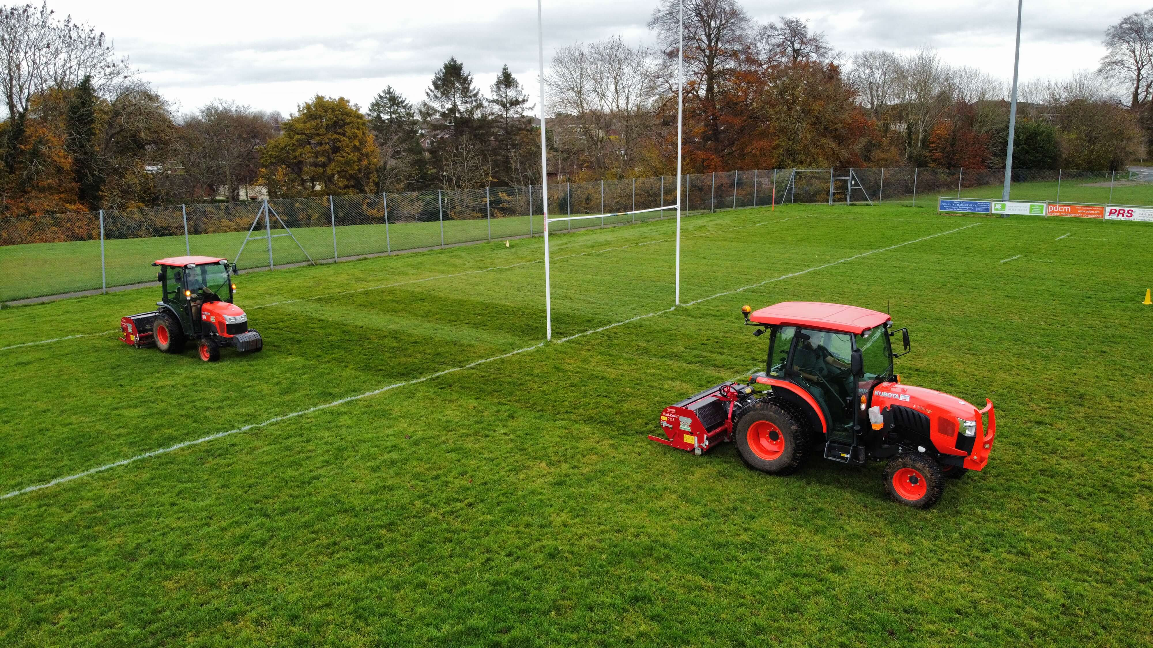 True tractors and aerators working on a rugby pitch