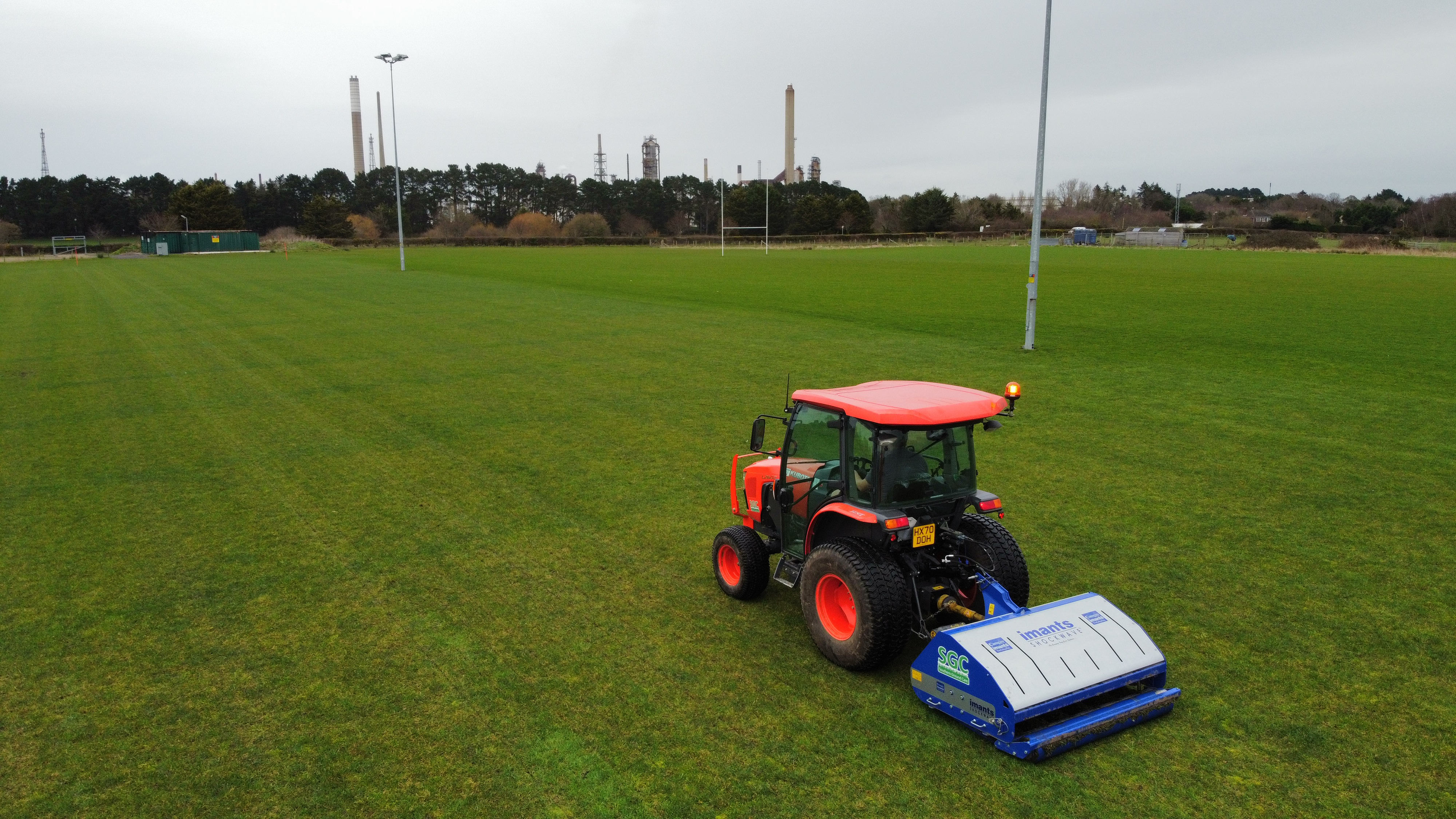 A tractor with shockwave aerator on a rugby pitch