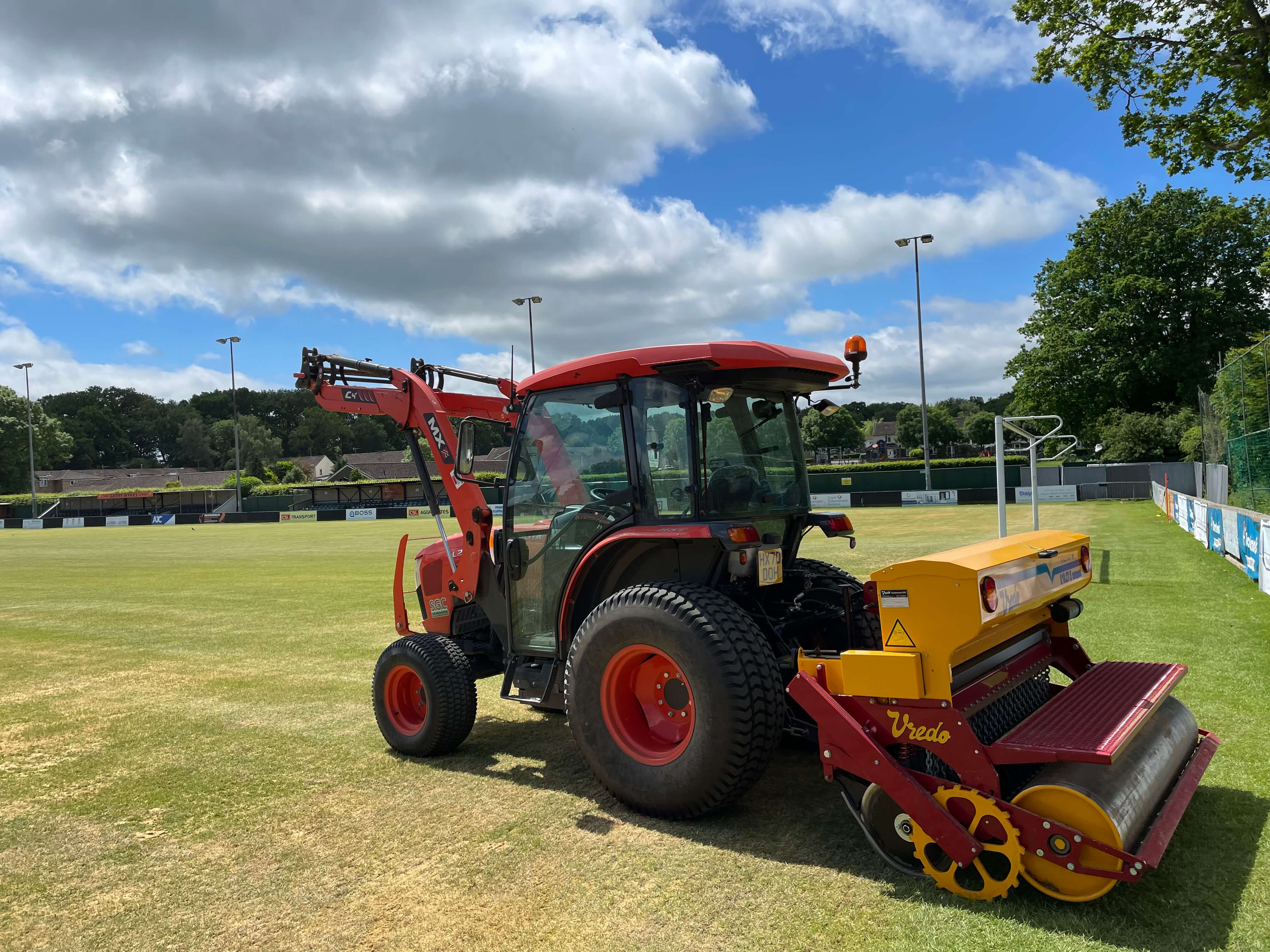 Tractor with seeder on football pitch