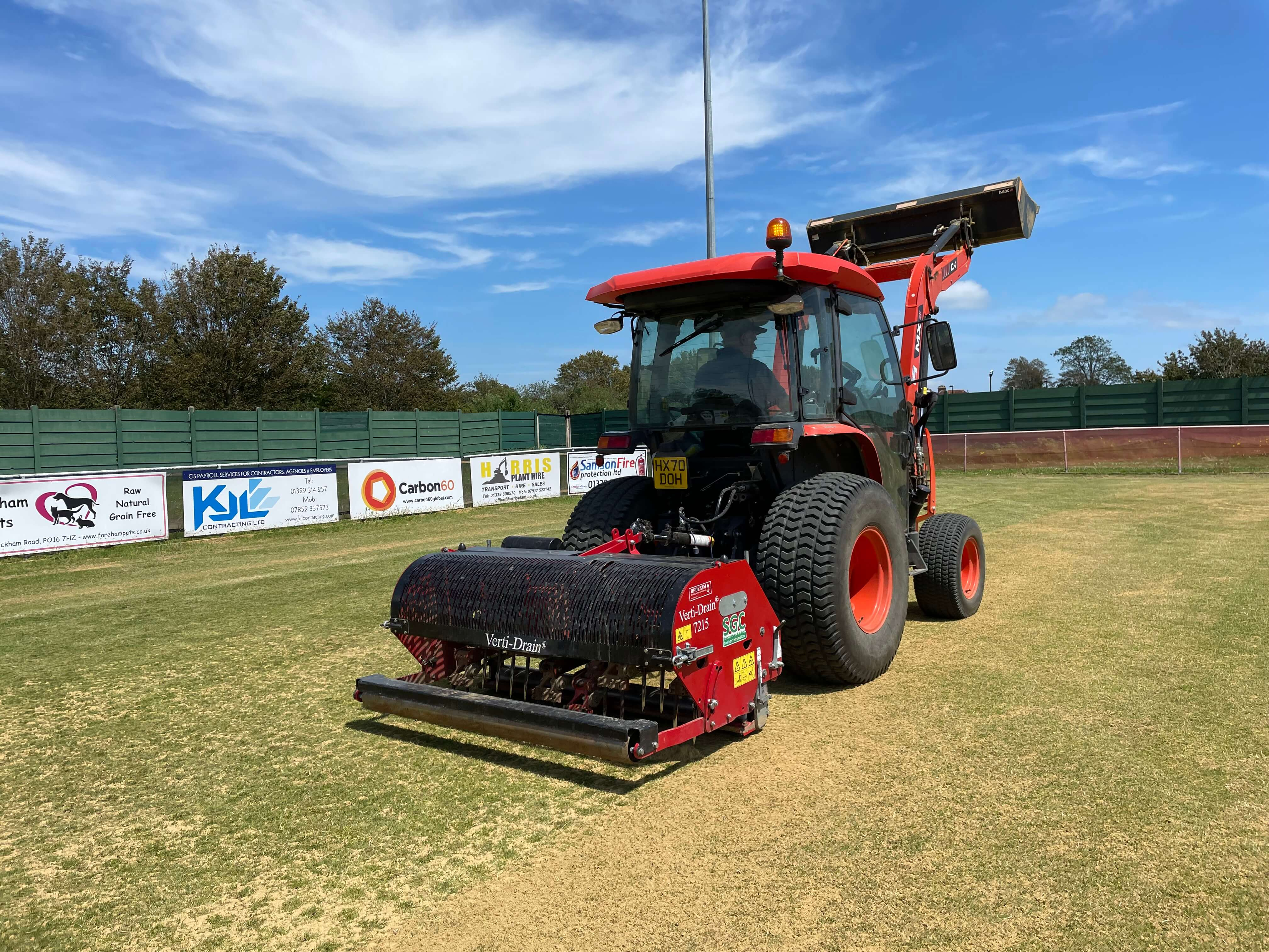 A tractor spiking sand in to a football pitch