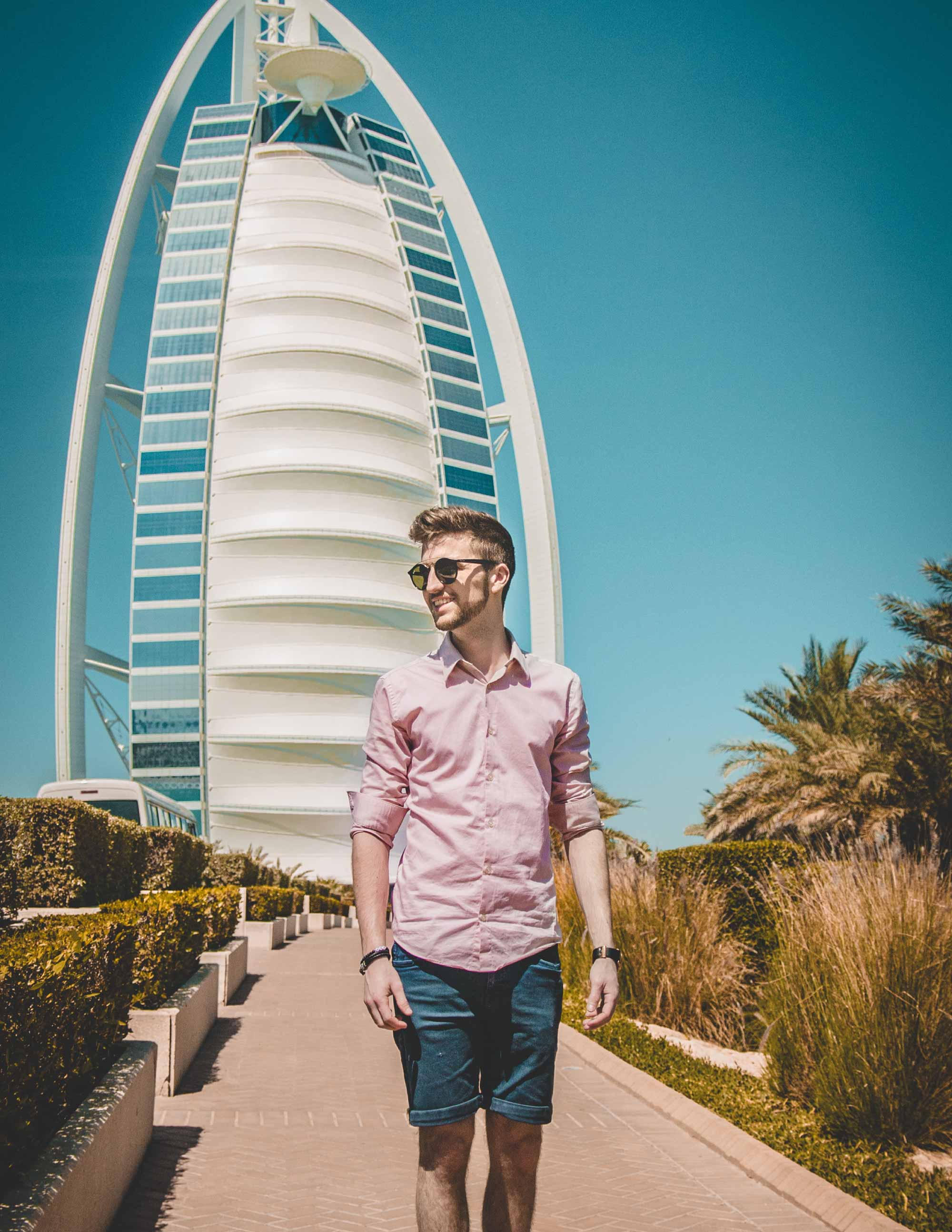 a young man in a pink shirt walks along a planted path in front of the Burj Al Arab in Dubai