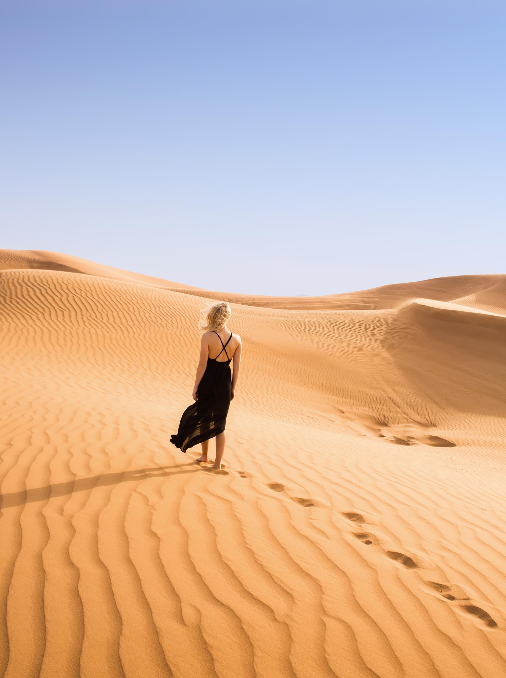 girl in black dress walks through the sand dunes of the desert in Dubai
