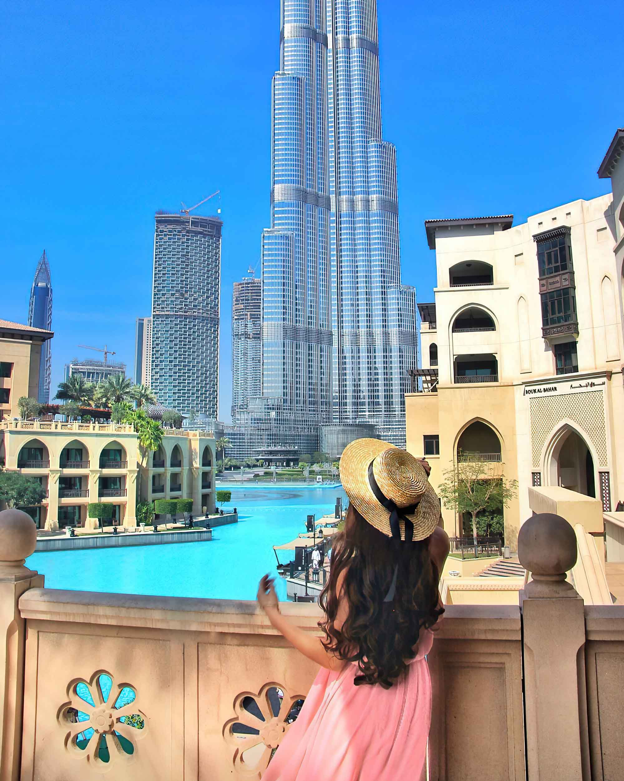 A girl in a pink dress and straw hat views the Burj Khalifa from across the decorative pools.
