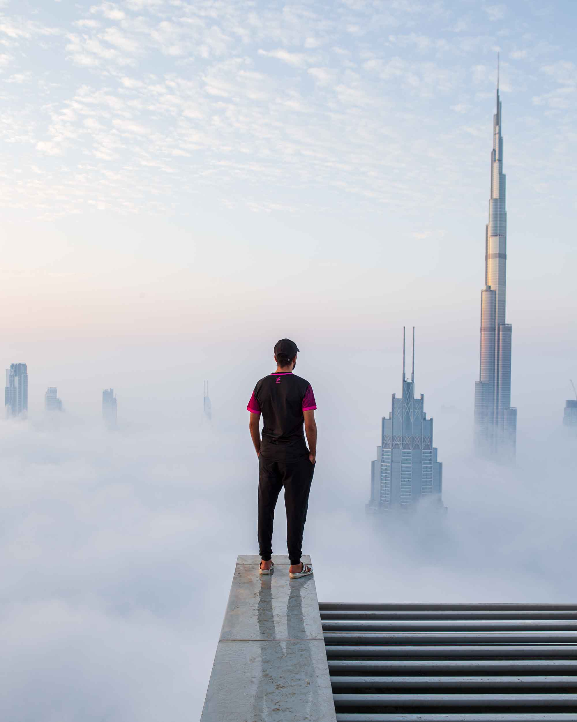 A man stands on top of an extremely high building, overlooking the skyscrapers of Dubai push their way through a thick white cloud.