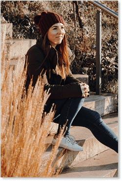 Melanie Lindeman sitz auf eine Treppe und guckt in die Ferne