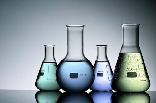 Four science lab beakers on a desk filled with chemicals