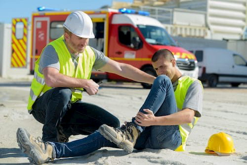 Injured construction worker holding his shin and his boss rendering help