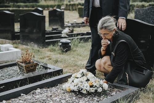 Grieving widow, wearing black, crouched over a tombstone at a funeral
