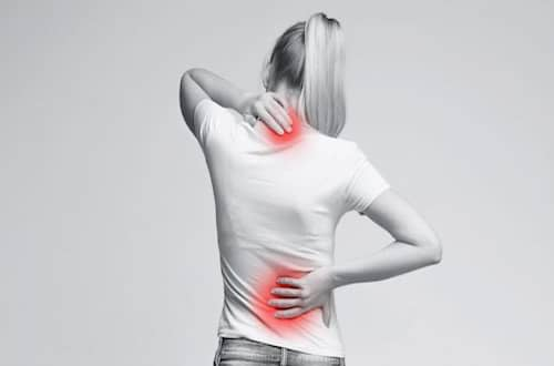 Woman holding her painful neck and low back