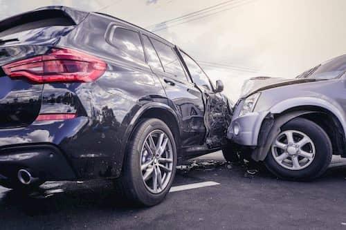 Car crash of a Gray SUV hitting a dark SUV