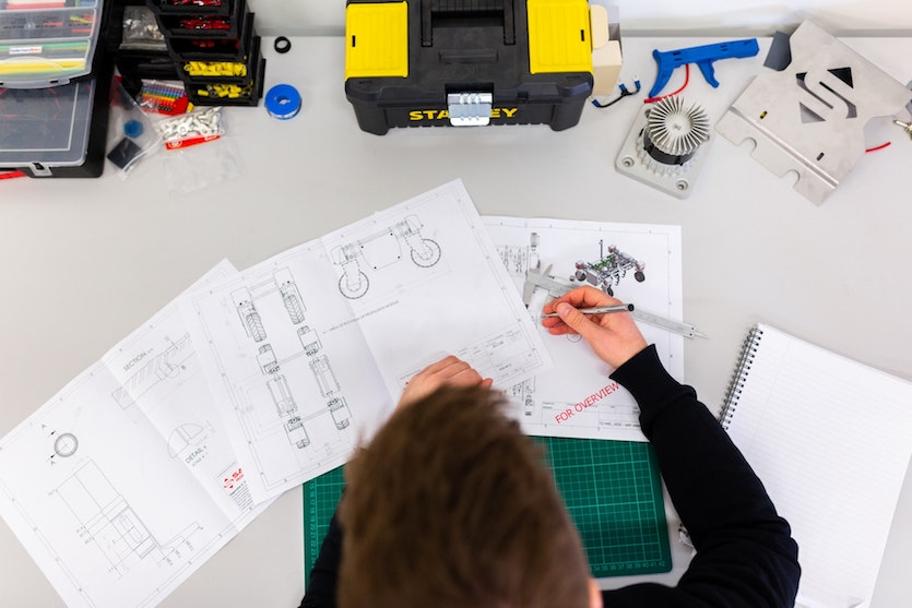 Top view of a person drawing blueprints of a machine with tools, papers and notepad around him. Photo by ThisisEngineering RAEng on Unsplash