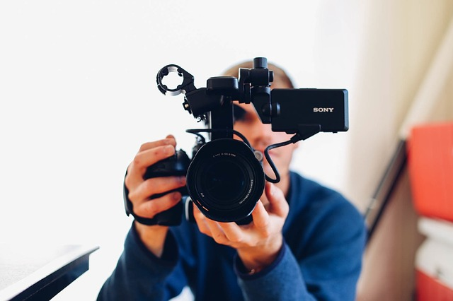 Man with video camera pointing at you and recording