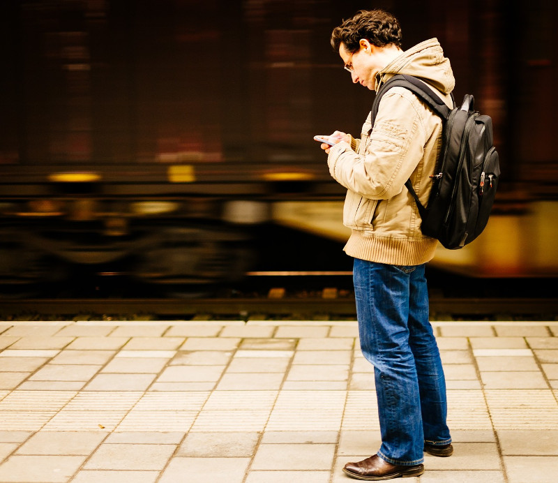 Guy with mobile phone waiting at a train station