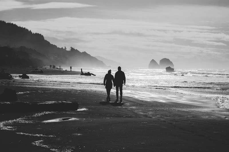 Couple walking on low tide beach