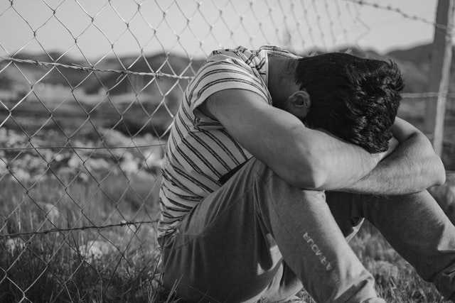Black and white photo of man sitting on ground beside wired fence with his head on his arms