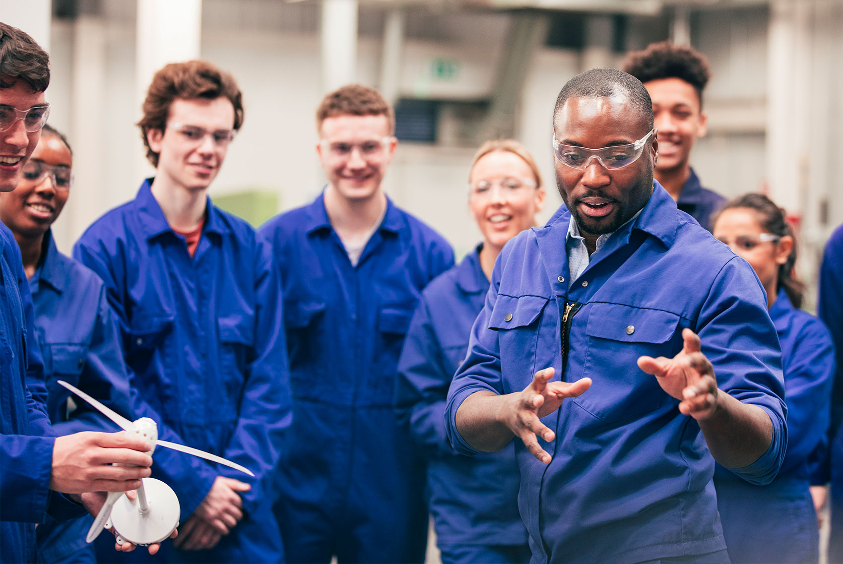 A diverse group of young adults are in an industrial setting. They watching as a middle-aged man is demonstrating something off camera.