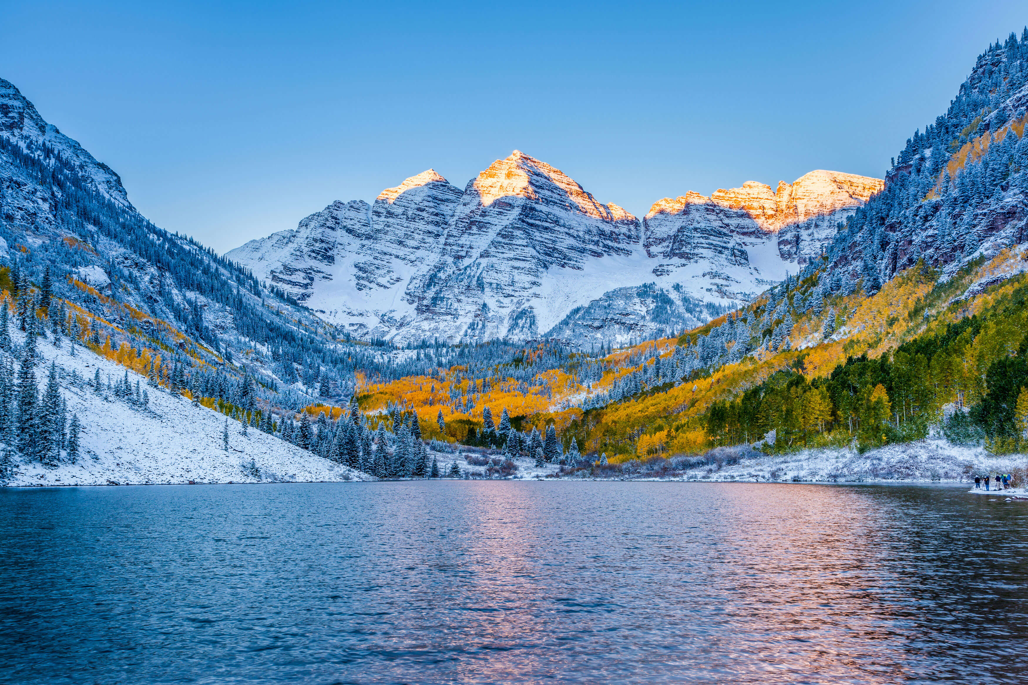 A landscape photo of snowy mountains and the reflection of a sunset in a lake