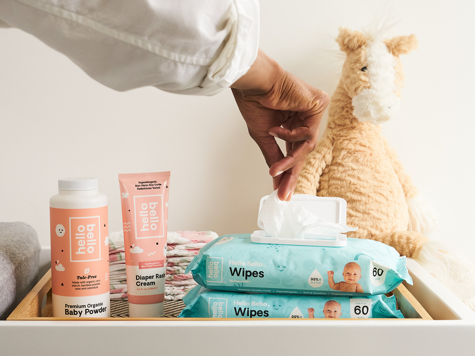 Hello Bello lifestyle image of a person opening a container of baby wipes. Featuring baby wipes, diaper rash cream, and baby powder.