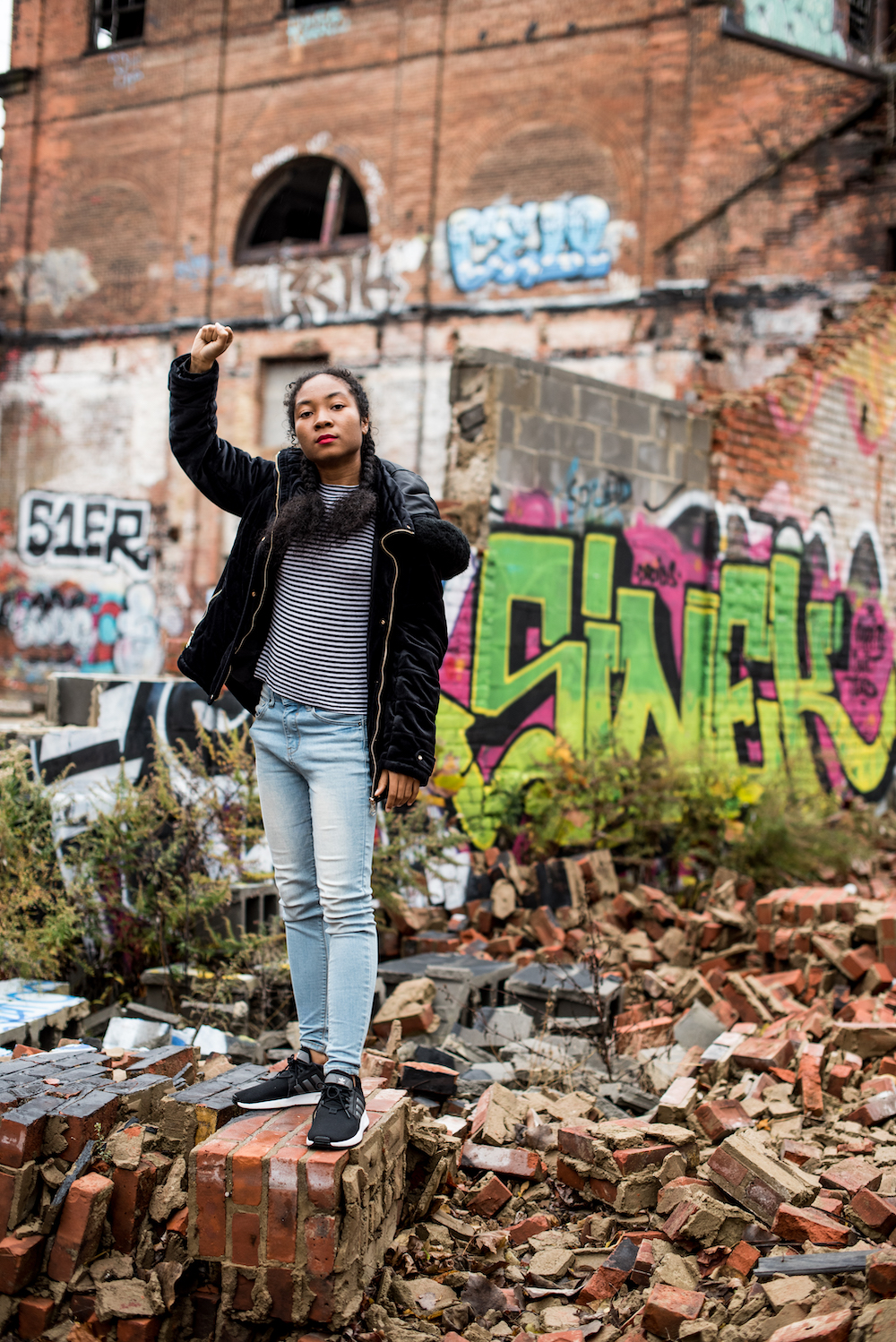 Woman standing in front of graffiti with fist lifted in the air