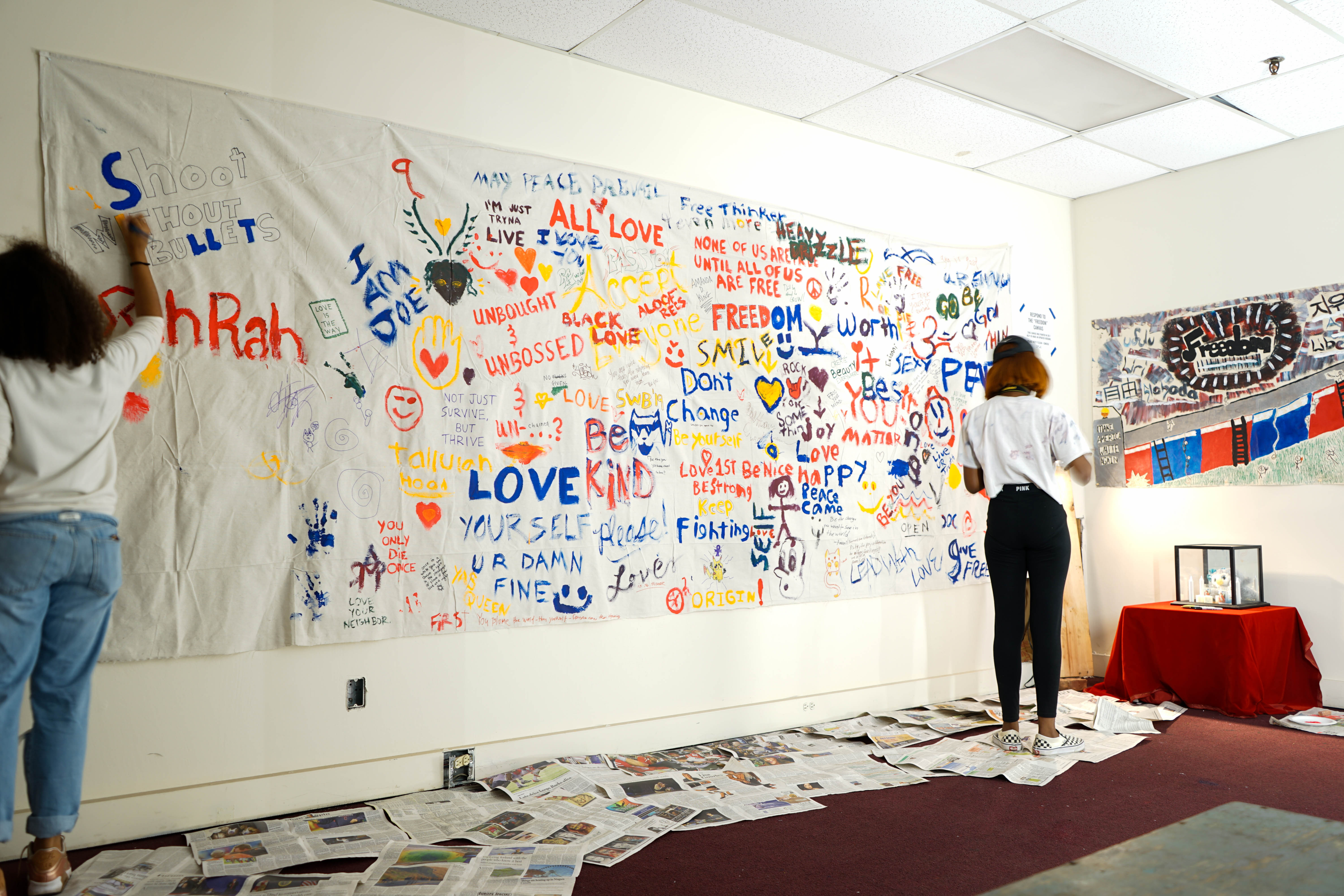People painting words on canvas