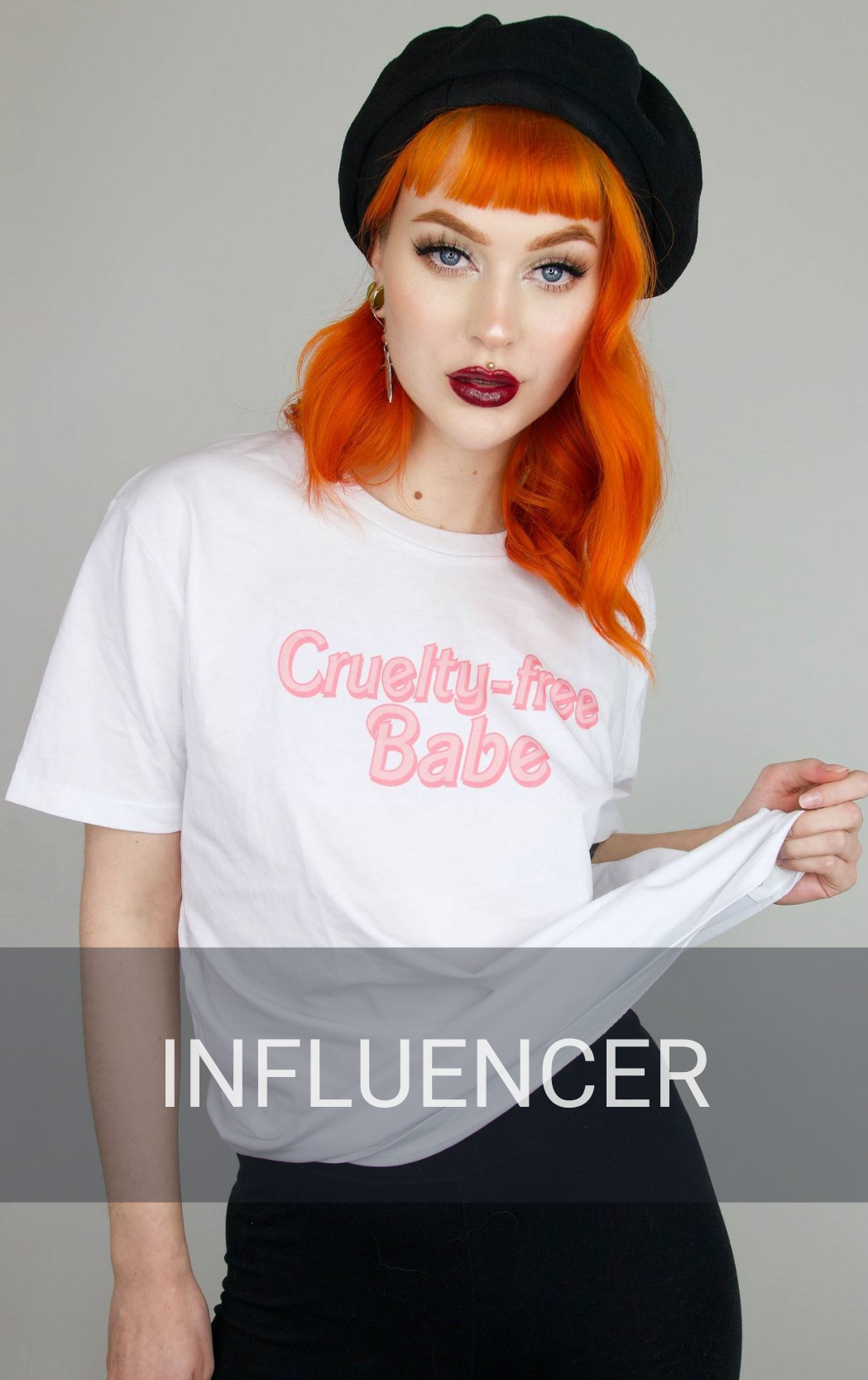An influencer wearing her own branded clothing collection. She has red hair and is wearing a white t-shirt facing a camera.