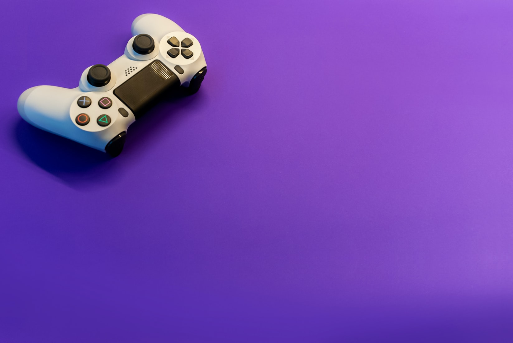 a videogame controller on a purpel background