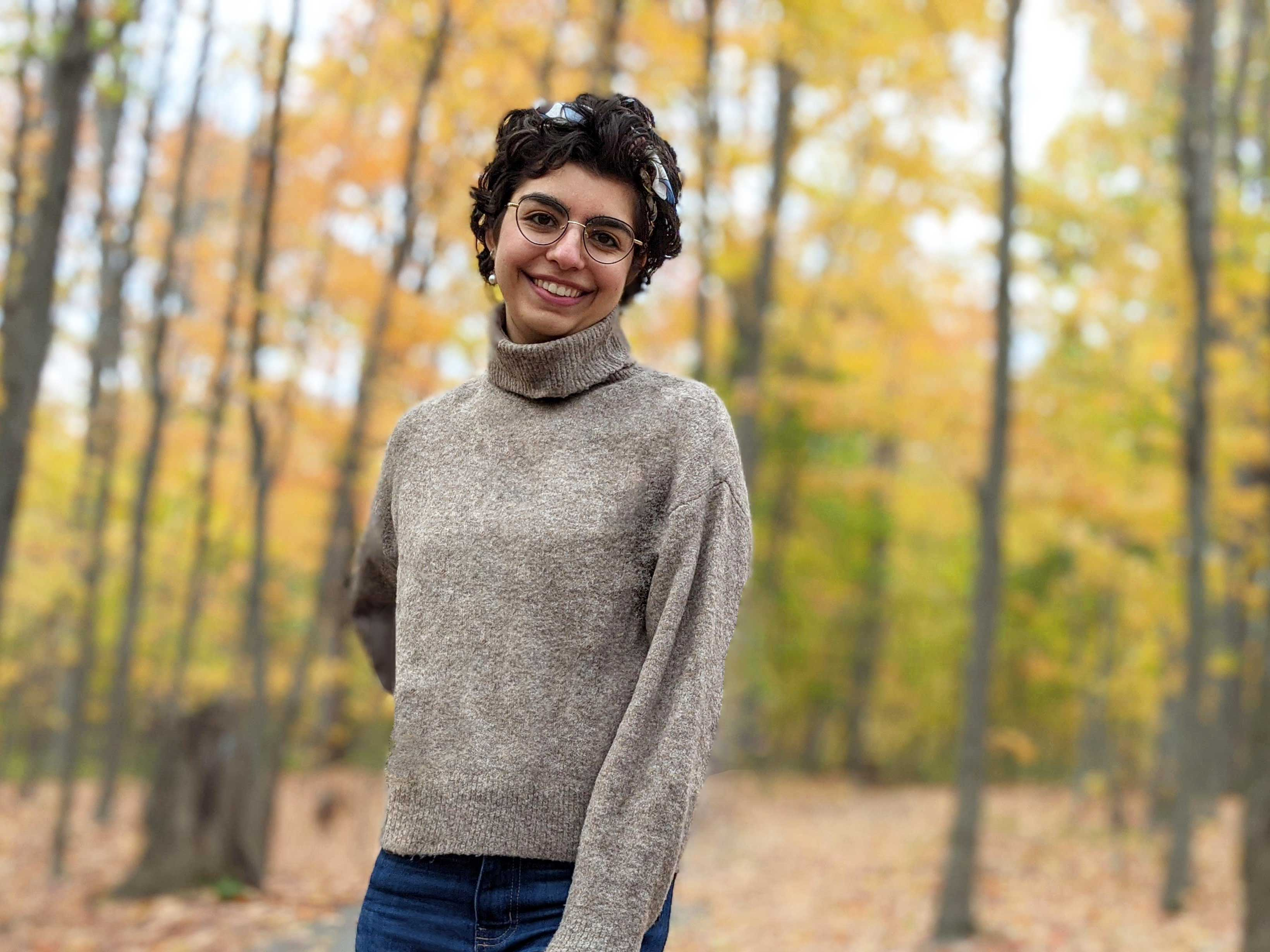 Dana smiling, wearing a turtle neck sweater in the woods