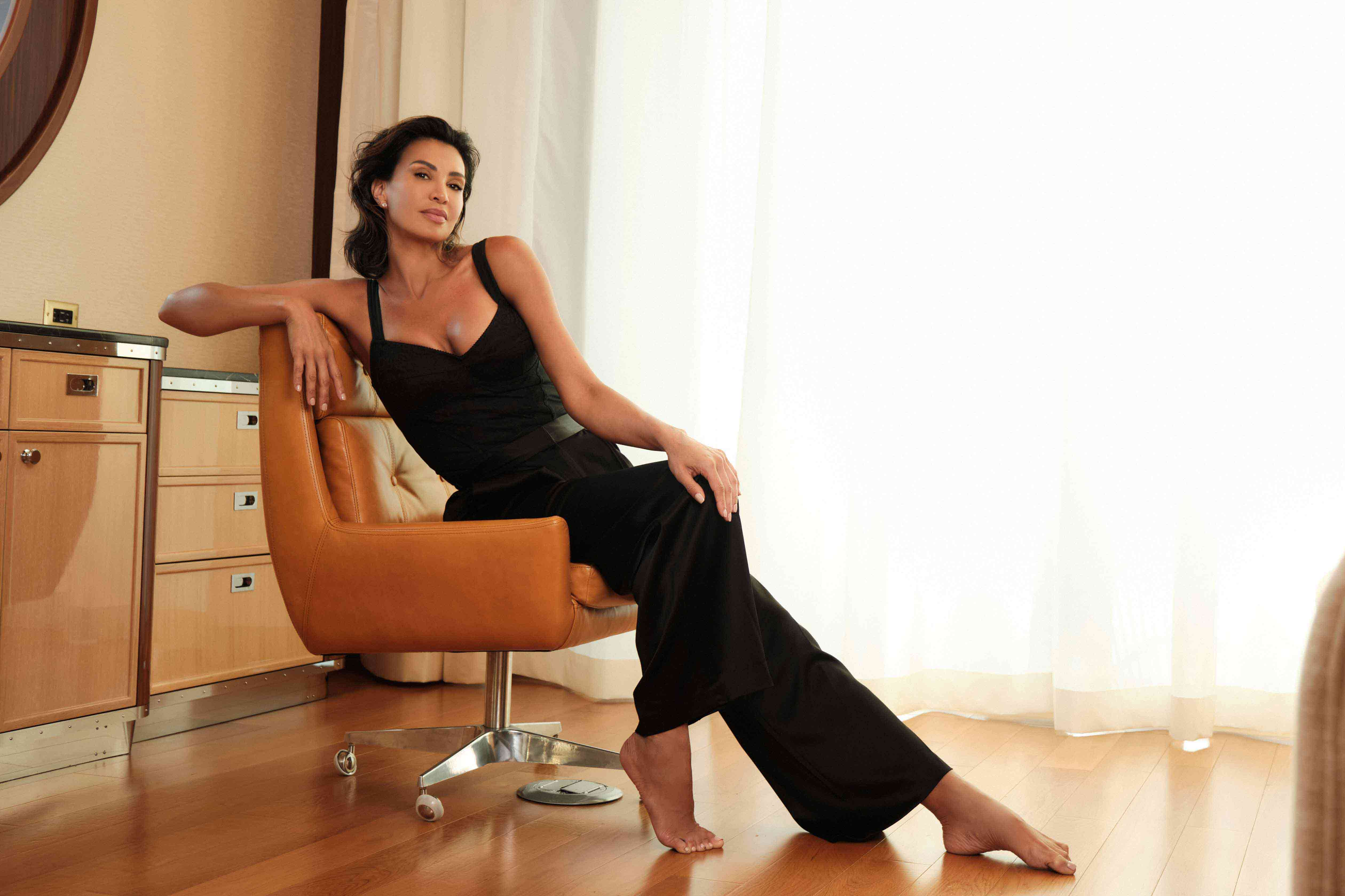 Debora Castaneda, CEO of Beatala, posing on a  light brown leather office chair, Mr. C Miami Suite, Florida