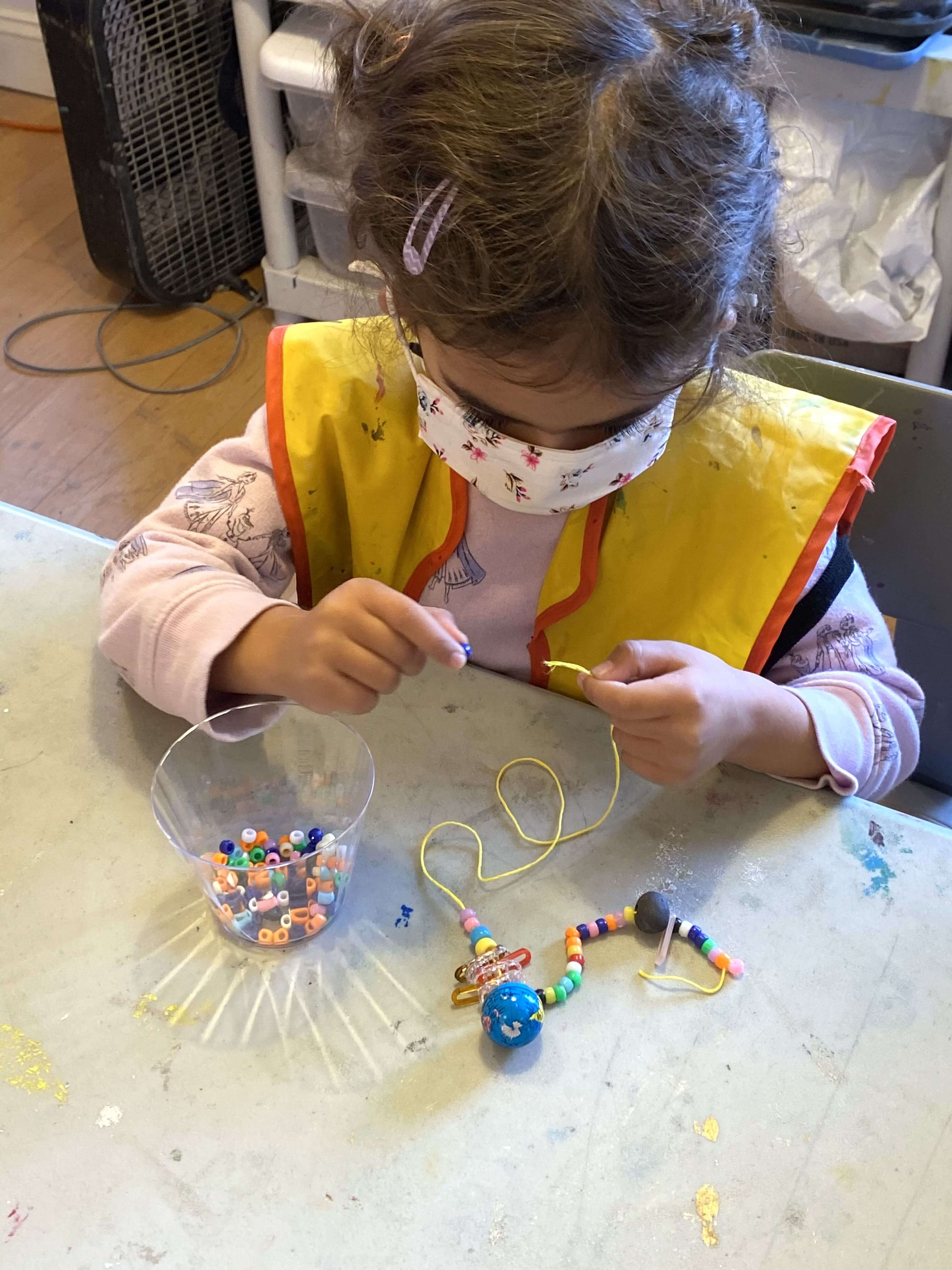A picture of a girl making a necklace