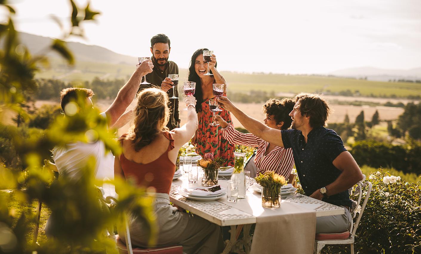 Un gruppo di amici a tavola passano il tempo allegramente mangiando le DOP Piacentine  e brindando con vino rosso