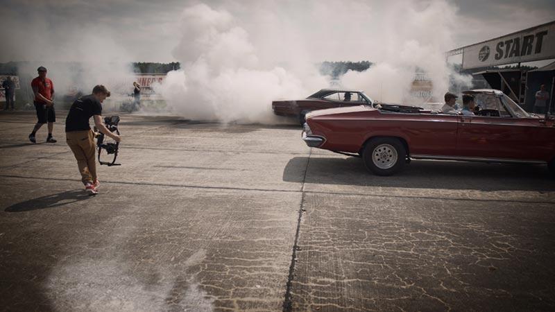 Man filmar med gimbal bakom bilar
