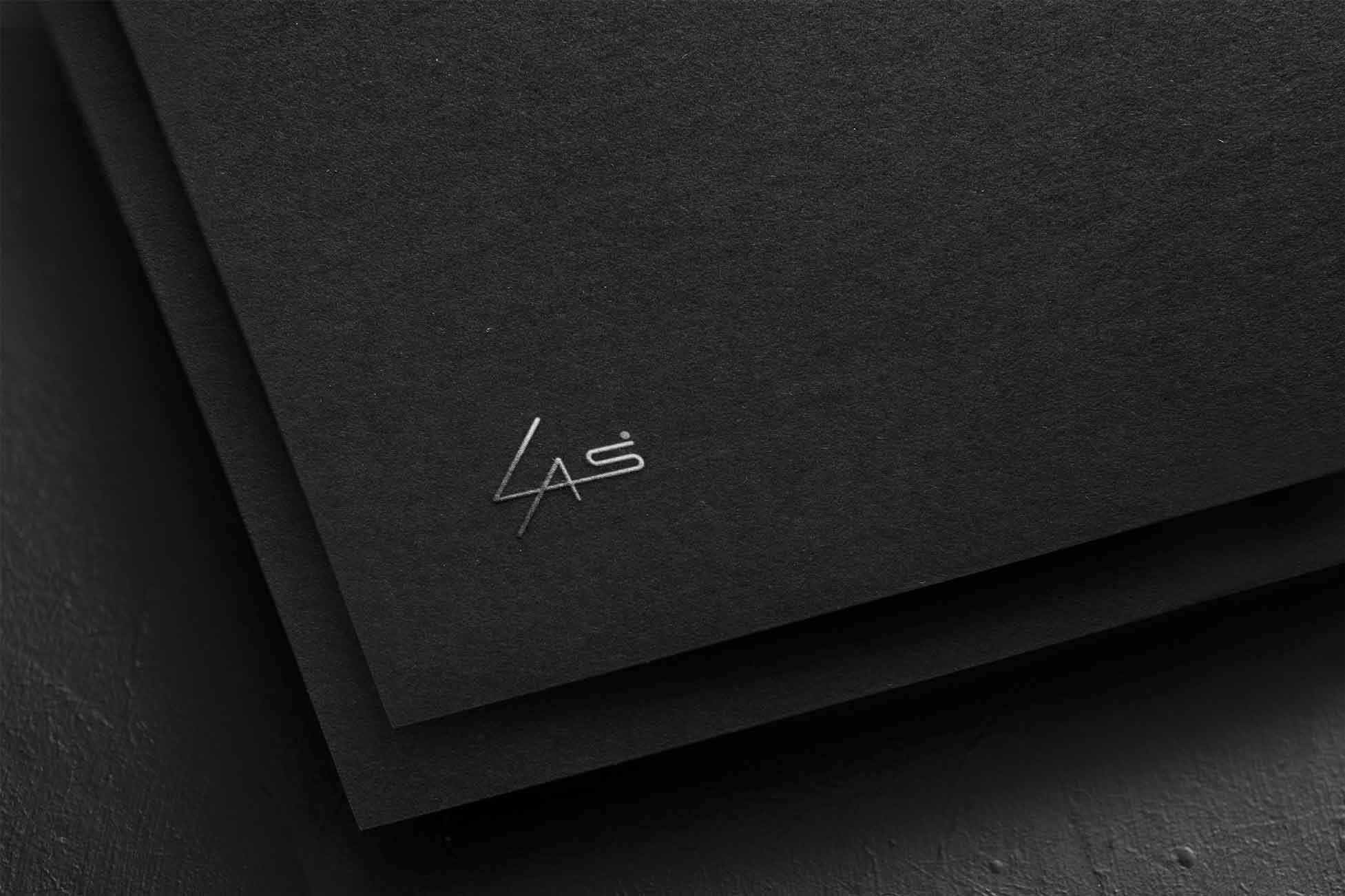 Silver LAS Design logo printed on black paper