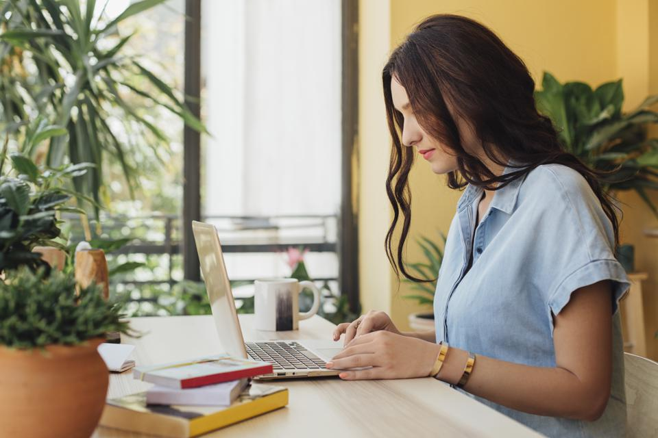 Caucasian woman using laptop at desk