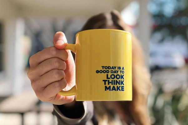 """An employee holding up a yellow mug that says """"Today is a good day to look think make."""""""