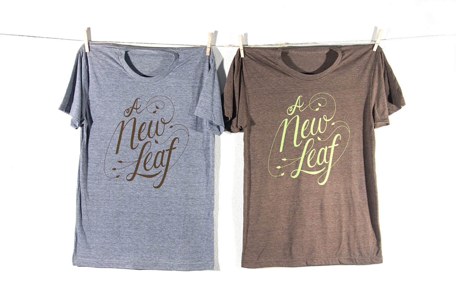 """Two Crossvine t-shirts hang from a clothesvine with the scripty hand-lettered slogan """"A New Leaf."""""""