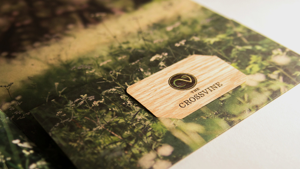A wooden Crossvine business card tucked into a custom branded folder.
