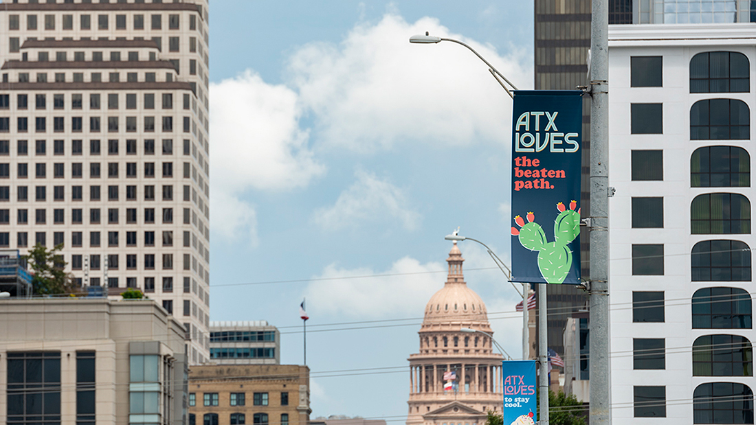 A sign on a street lamp in downtown Austin that reads ATXLoves: The Beaten Path, with an illustration of a cactus.