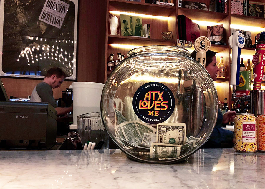 """A sticker on a fishbowl at a movie theater that reads """"ATXLoves Me."""""""