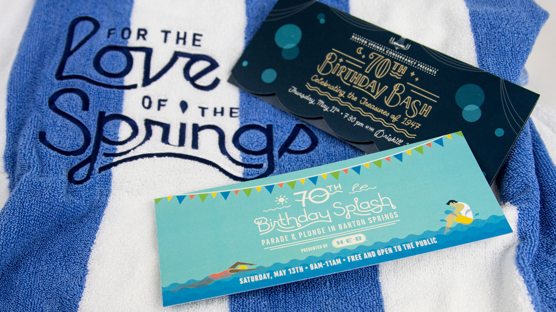 """An illustrated invitation for a Barton Springs Conservancy fundraiser on top of a custom towel that reads """"For the Love of the Springs."""""""