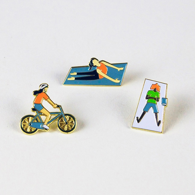 Three enamel pins of illustrative characters in the park.
