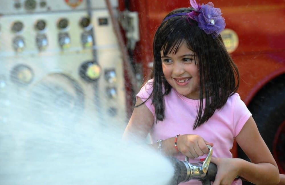 Young girl spraying water.