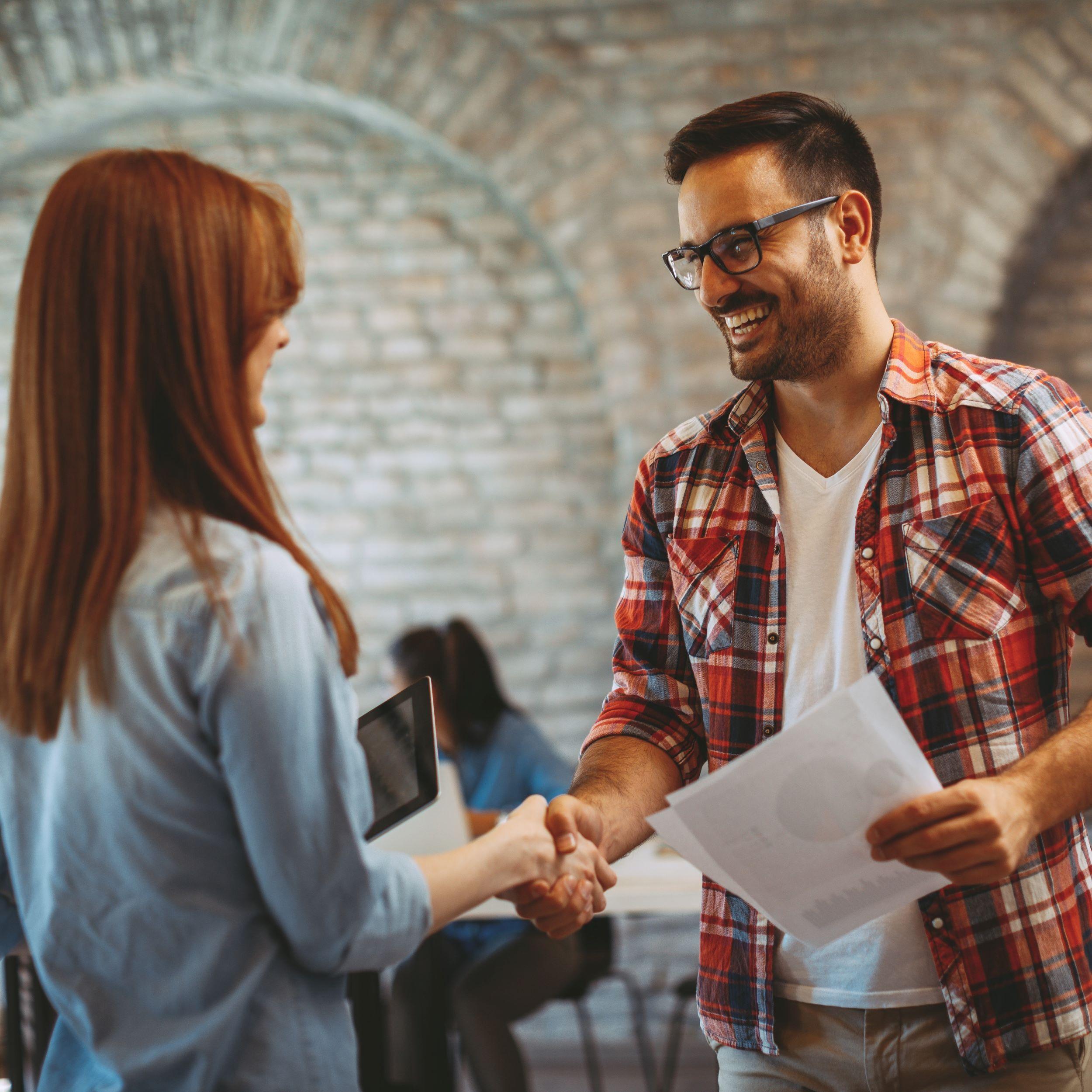 Two people shake hands in moonshot brands partnership program.