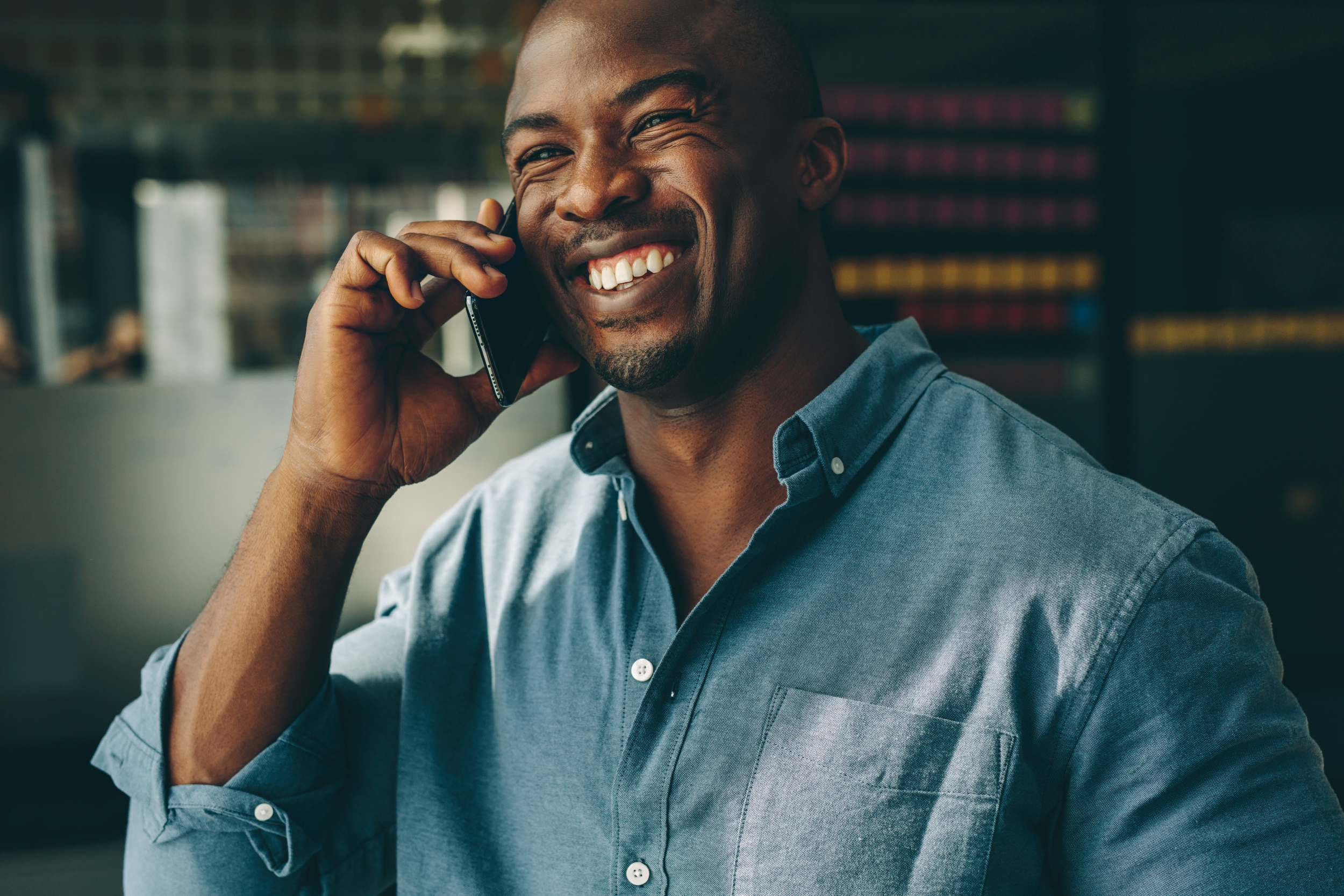A confident, handsome black man speaks on the phone with a consultant about his business exit strategy