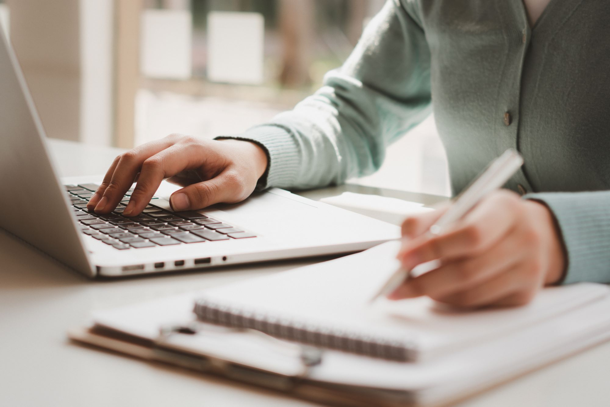 A white woman works on a computer going through her business transfer checklist